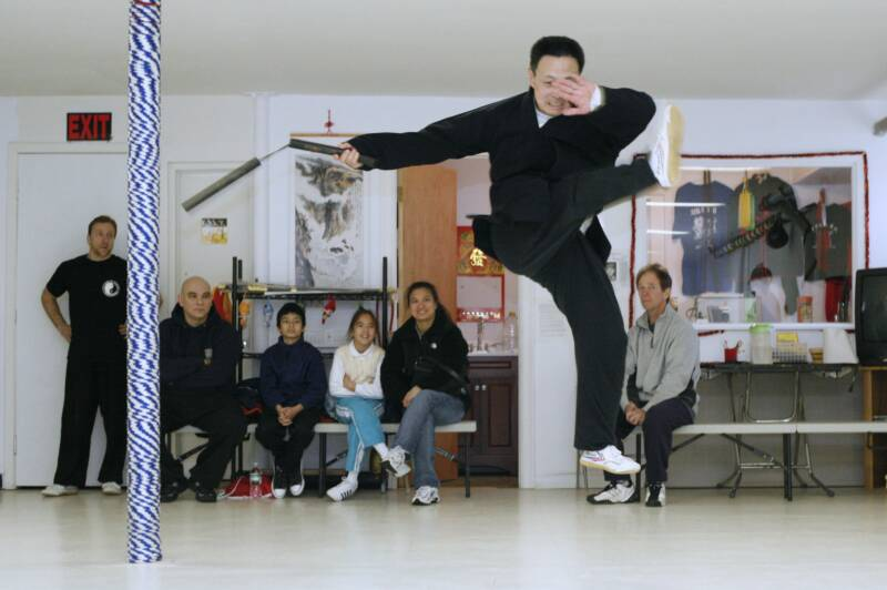 Grandmaster Li Tai Liang showing kung fu jump kick holding a nunchaku